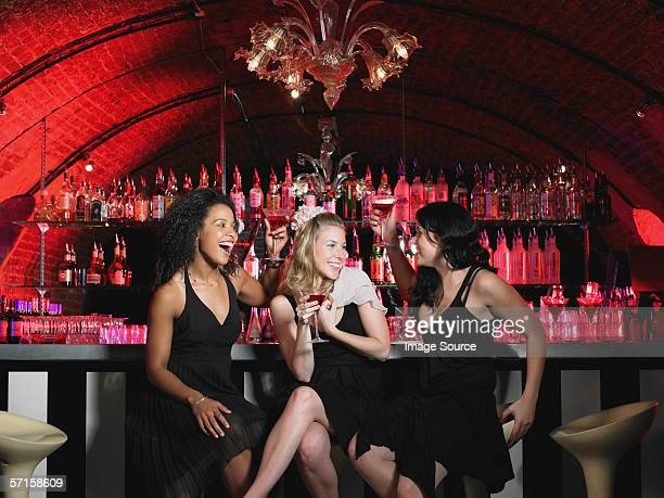 Three women sitting at bar