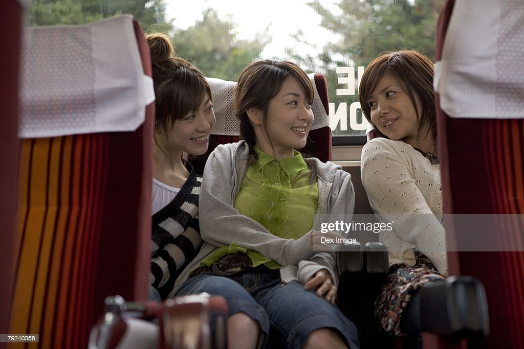 Three women sitting at the back of a bus : Stock Photo