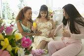 Three women sitting on sofa, two feeling pregnant woman's bump