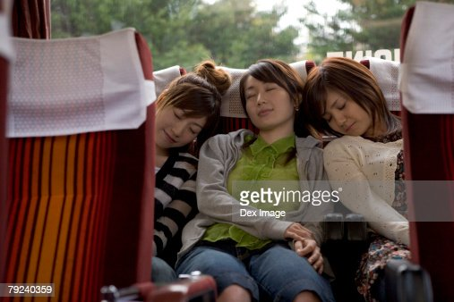 Three women sleeping at the back of a bus : Stock Photo