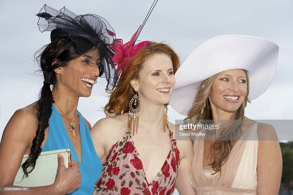 Three women smiling at the races