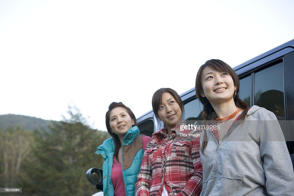 Three women standing next to car : Stock Photo