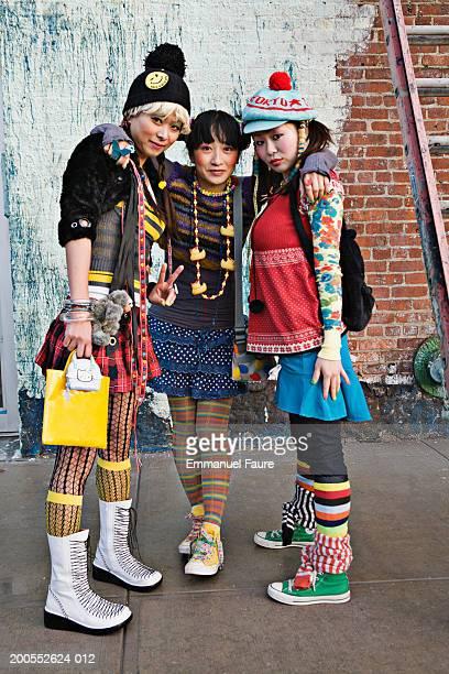 Three women standing on sidewalk, portrait