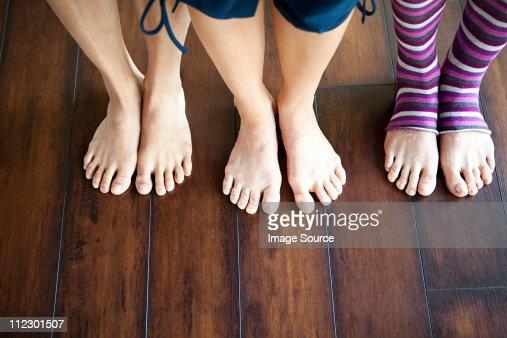Three women standing on wooden floor