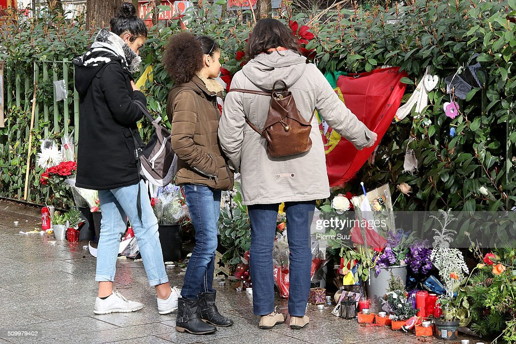Three women stands in front of the tributes to the victims of the Paris Attacks across the road from of 'Bataclan Cafe'on February 13, 2016 in Paris, France. People continue to leave tributes to victims three months after the Paris terrorist attacks.