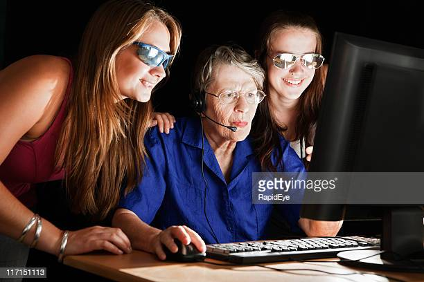 Three women study computer screen intently