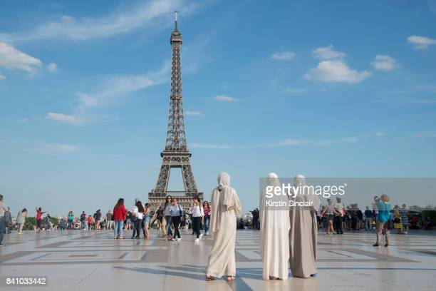 Three women take mobile phone photographs and selfies in front of the Eiffel Tour in day 3 of Paris Haute Couture Fashion Week Autumn/Winter 2017 on...