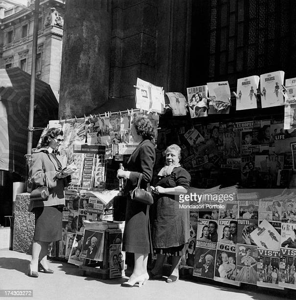Three women talking outside a newspaper kiosk Italy May 1954