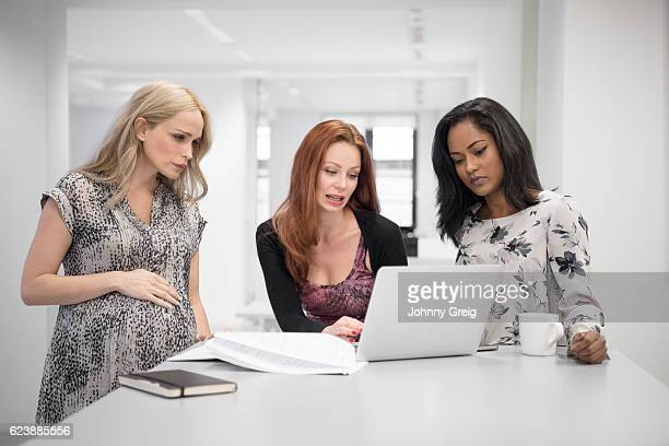 Three women using laptop, pregnant woman with hand on stomach