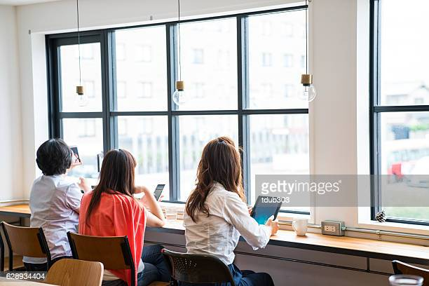 Three women using wireless technology in a cafe