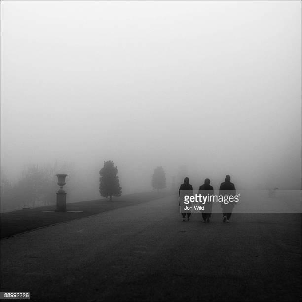 Three women walking in fog