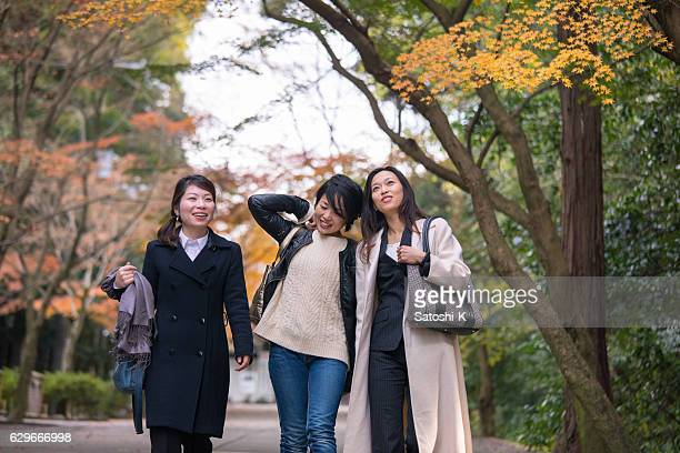 Three women walking together under autumn foliage with smile