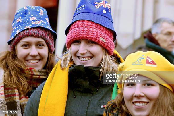 Three women wearing hats picturing Australian National flag pose as they attend the Anzac day in tribute of Australians and New Zealanders soldiers...