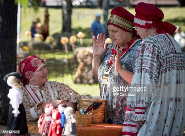 Three women wearing traditional costumes talk at a park in Yekaterinburg during a folk fest for the celebrations of the 294th anniversary of the city...