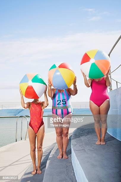 Three women with beach balls at pool