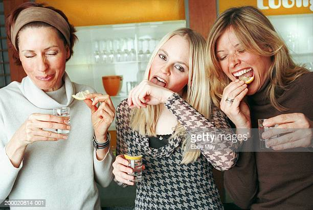 Three women with tequila shots, one licking salt from hand