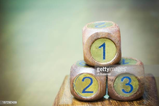 Three wooden dice with blue numbers