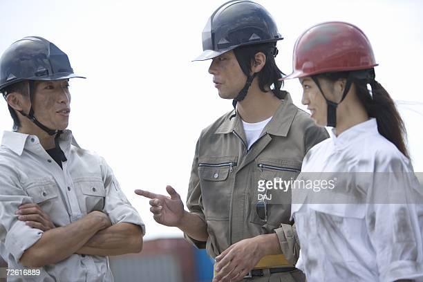 Three workers talking, Side View, Differential Focus