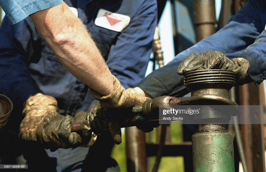 Three workmen pulling wrench at oilfield, close-up