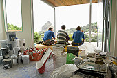 Three workmen taking break in house under reconstruction, rear view