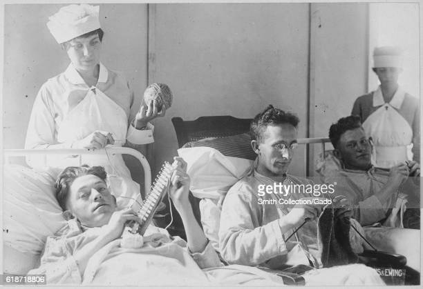 Three wounded soldiers knit from a hospital bed at Walter Reed Hospital Washington District of Columbia 1917 Image courtesy National Archives