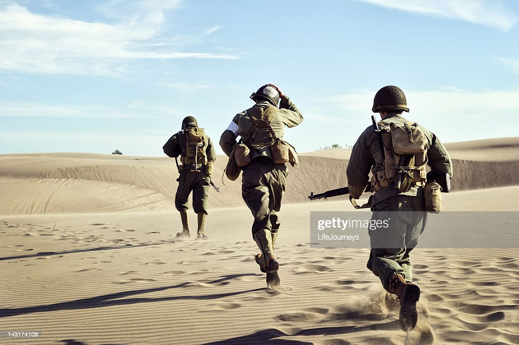 Three WWII Soldiers Running In The Desert Sand : Stock Photo