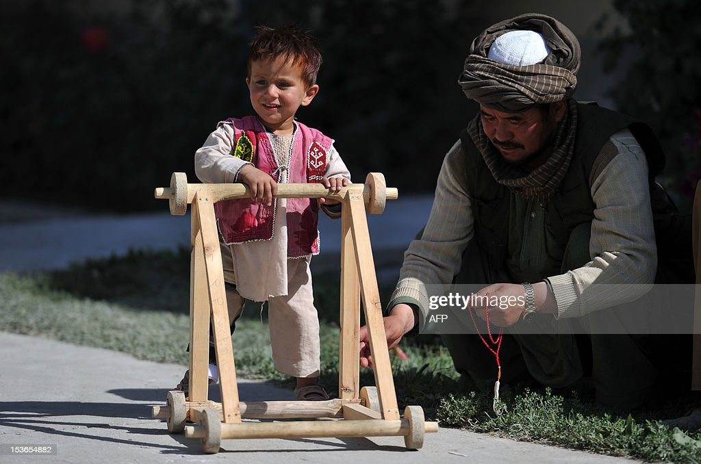 A three year old Afghan child patient who lost his leg in a suicide attack in Kandahar walks with the aid of a stroller at The International Red Cross Centre (ICRC) in Kabul on October 8, 2012. The Afghan government could implode after NATO troops pull out in 2014, particularly if presidential elections are fraudulent, a report by the International Crisis Group said.