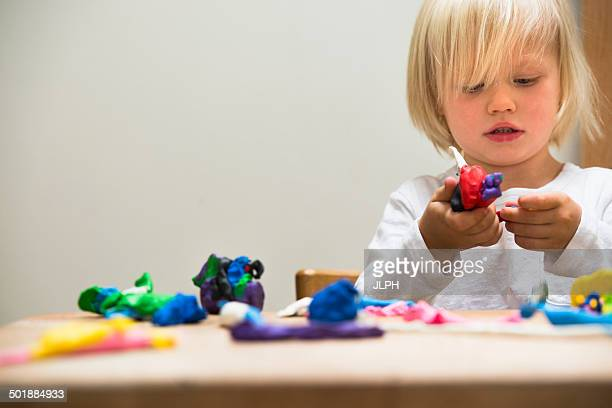 Three year old boy playing with modeling clay