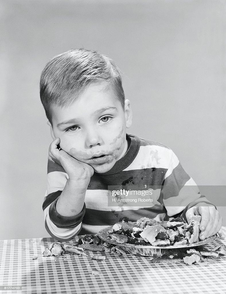 Three year old boy with blueberry pie smeared on face, taking part in pie eating contest. : Stock Photo