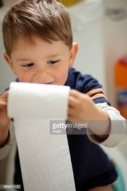 Three year old boy with roll of toilet paper