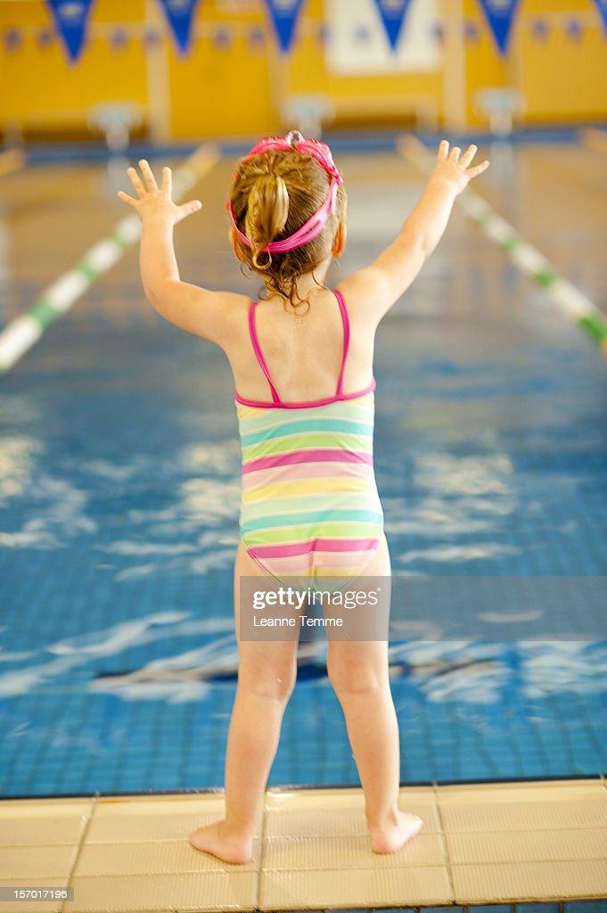 three year old girl standing on pool edge : Stock Photo