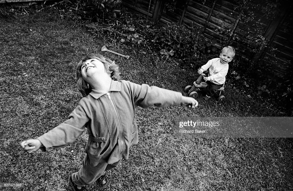 A three yearold girl throws her head back with joy while playing with her young oneyearold brother in the back garden of their South London home We...