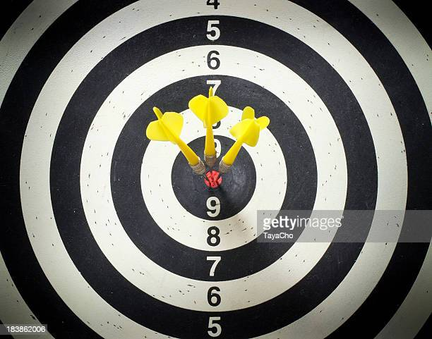 Three yellow darts in the black and white dartboard bullseye