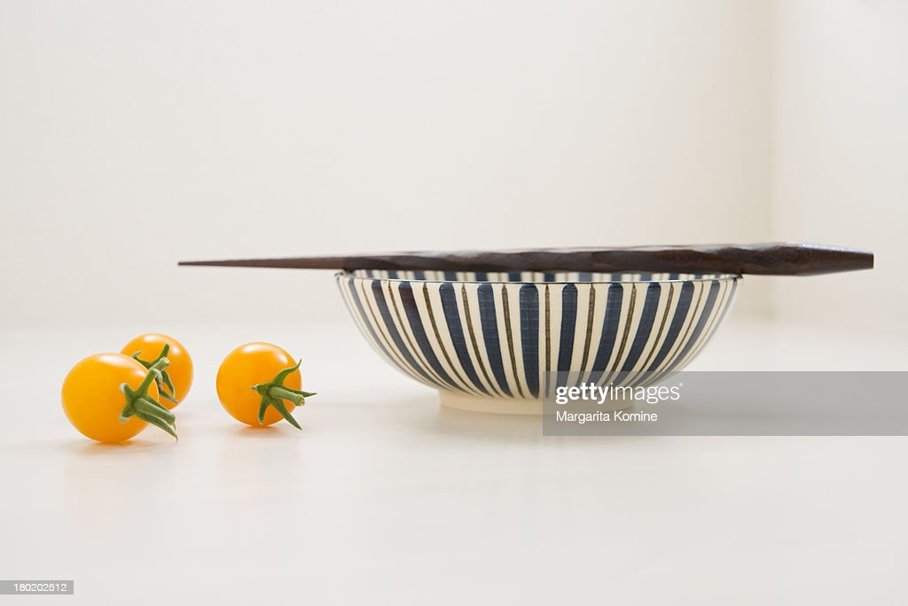 Three yellow tomatoes and a bowl with chopsticks