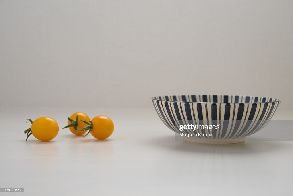 Three yellow tomatoes and a striped bowl