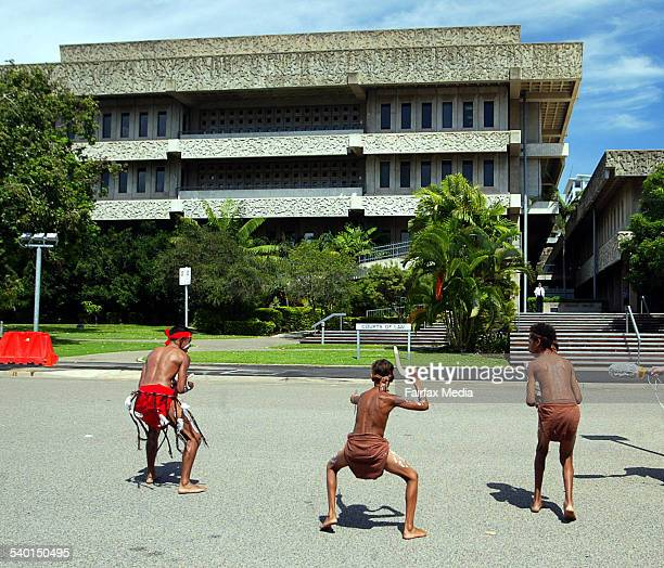 Three young Aboriginal men dance outside the Law Courts in Townsville during a protest over the death of Palm Island man Cameron Doomadgee while he...