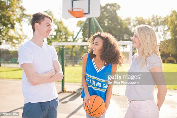 Three young adult basketball players chatting on basketball court