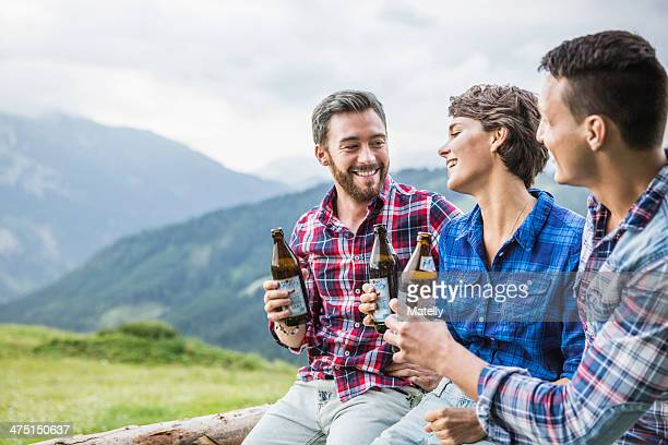 Three young adult friends drinking beer on fence, Tyrol Austria