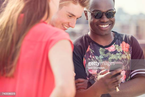 Three young adult friends looking at smartphone at roof party in London, UK