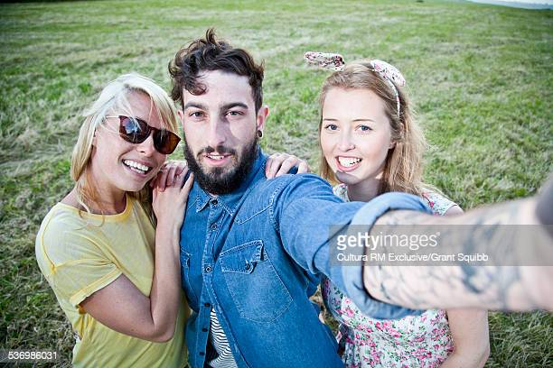 Three young adult friends posing for self portrait in field