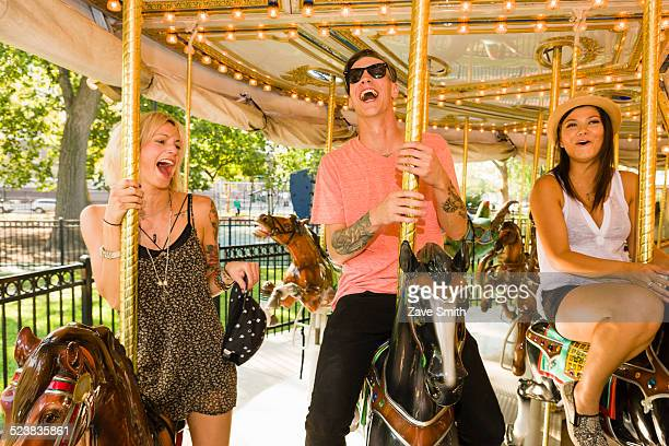 Three young adult friends riding horse carousel in park