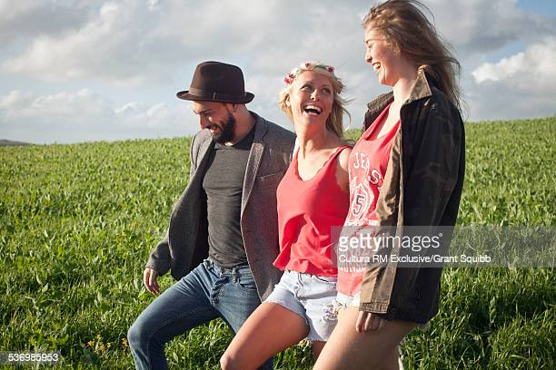 Three young adult friends strolling and chatting in grassy field
