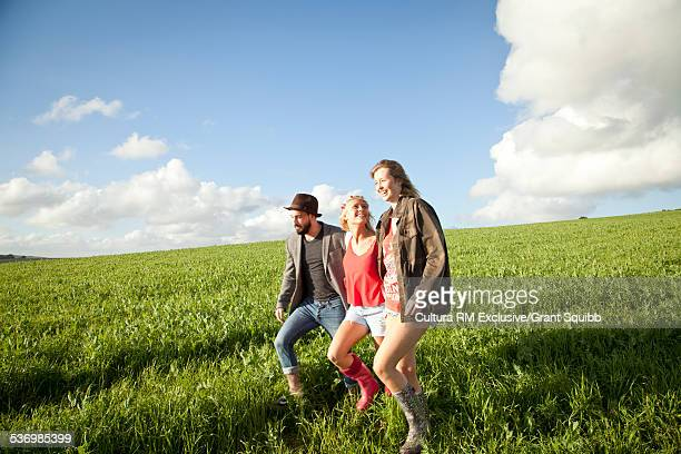 Three young adult friends strolling in grassy field