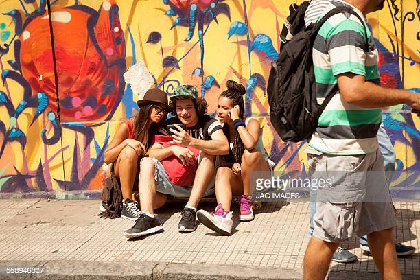 Three young adult hipsters sitting on sidewalk reading smartphone texts, Rio De Janeiro, Brazil