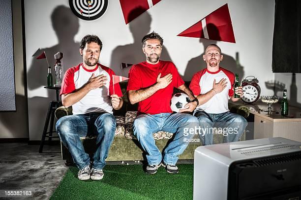 Tres hombres adultos jóvenes amigos viendo fútbol americano: Himno nacional orgullo