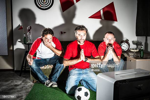 Three young adult men friends watching football: Penalty hope
