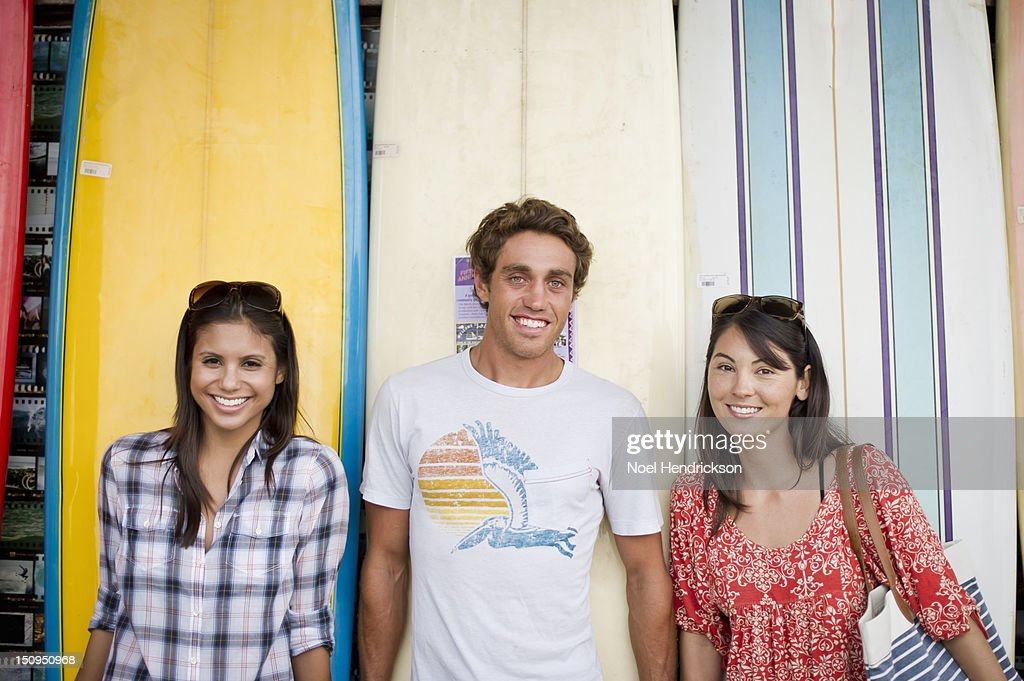 Three young adults in front of surfboards : Stock Photo