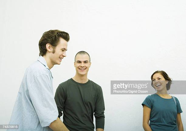 Three young adults, laughing, white background
