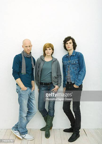 Three young adults leaning against wall, looking at camera, full length portrait, white background