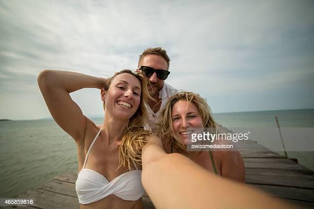 Tres adultos jóvenes en vacaciones tropicales tomando un autorretrato